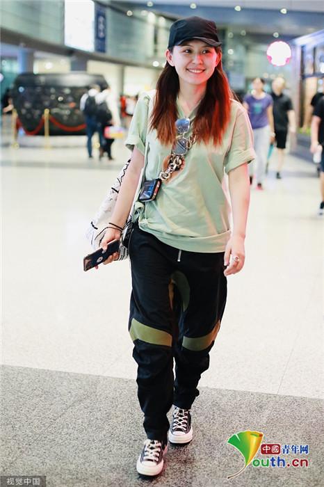 扎现身机场。她穿绿T配黑裤走